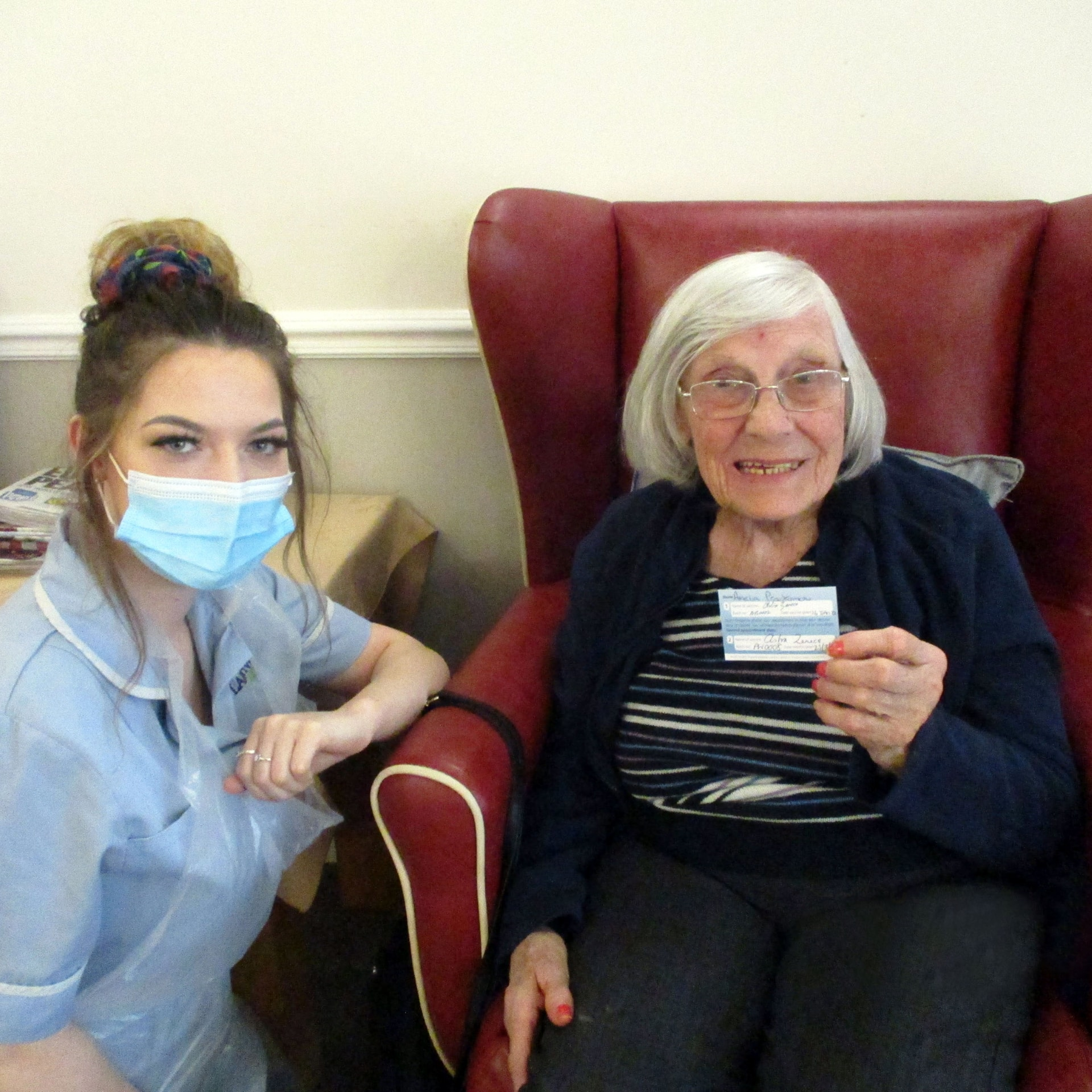 Ann Prodromou, aged 93, and Chantel Dickens, care assistant with Ann's Covid-19 vaccination card at Down Market-based care home Diamond House.