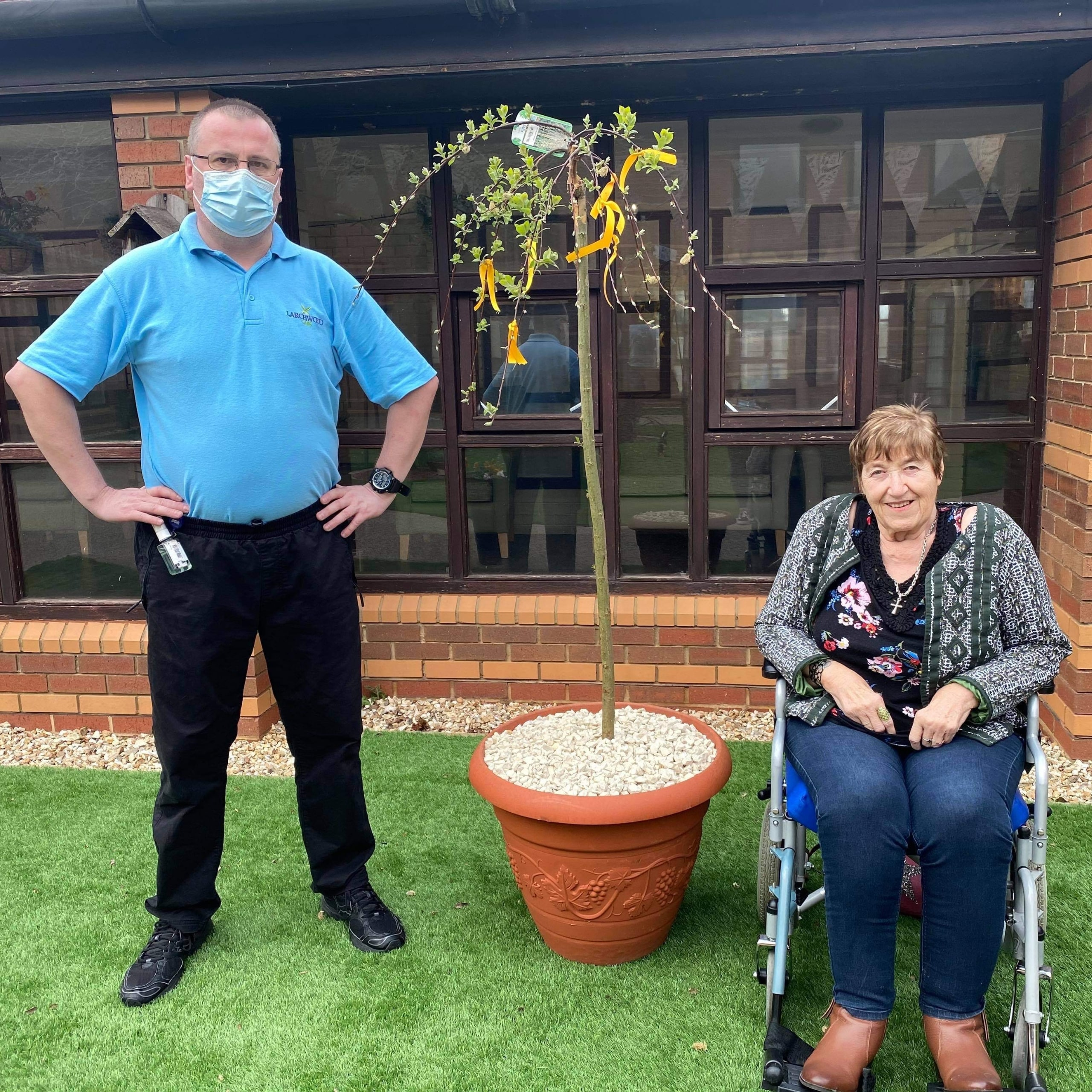 Oake Meadows Care Home resident Margaret Hill aged 77 and Wayne Farrington-Carter, Care Assistant with the home's memorial tree.