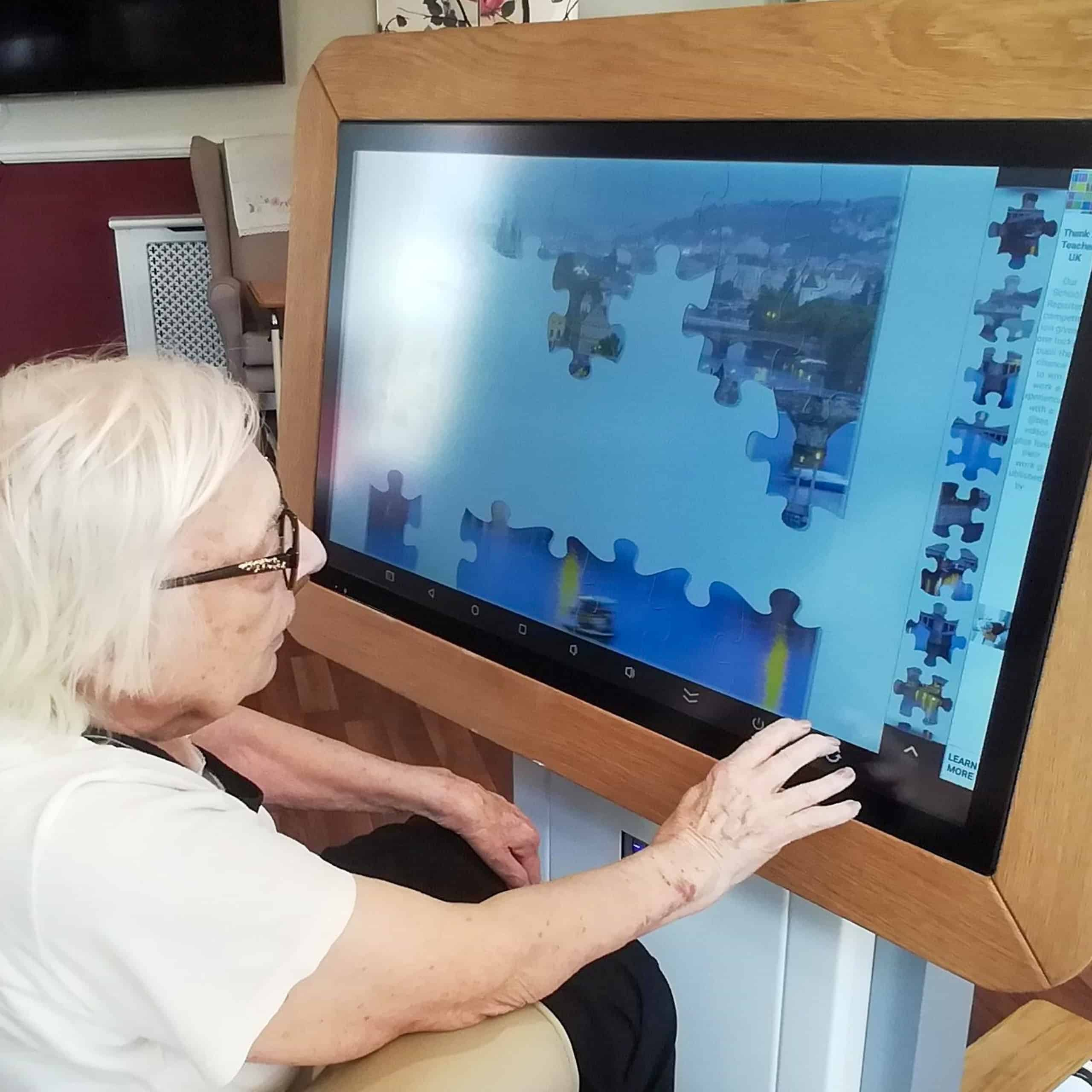 Stambridge Meadows Care Home resident, Joan Winsor enjoying a puzzle on the home's interactive table.